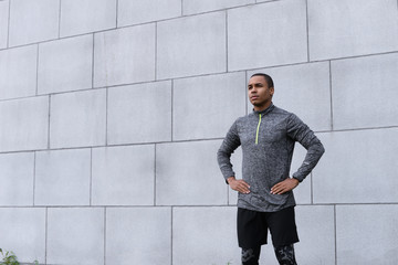 Tuinposter Fantasie Landschap Isolated cropped shot of attractive young Afro American sportsman in trendy sports clothes, standing at grey brick wall, keeping hands on his waist while relaxing after running exercise, feeling tired