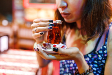 Woman tourist drinking delicious traditional Turkish tea in outdoor cafe at night