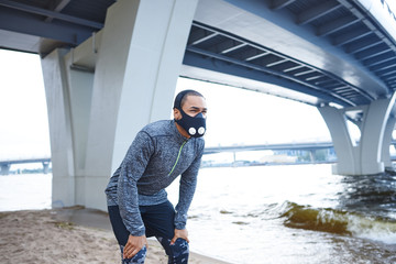 Lifestyle picture of tired young African American male runner in training mask resting, having break during evening running workout on city beach, catching his breath with hands on his knees