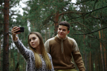 Charming pretty girl holding mobile phone while taking selfie, posing together with her smiling boyfriend over beautiful landscape with pines in background. People, nature and modern technology