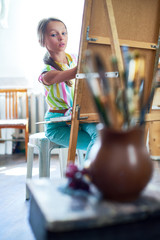Portrait of talented little girl painting still life picture on easel in art class looking at art supplies set up