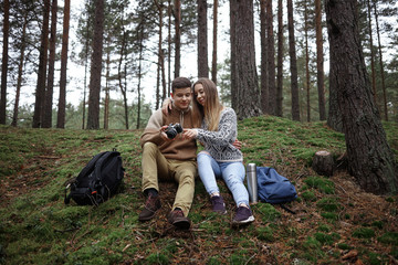 Handsome guy and beautiful girl wearing sensible clothes watching pictures on professional camera, sitting on grass close to each other among trees with backpacks and thermos bottle on the ground