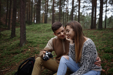 Cute shot of romantic couple resting in forest, sitting on grass and viewing photographs on camera. Professional male photographer showing pictures he took to his girlfriend while hiking in woods