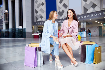 Portrait of two beautiful young women chatting in shopping mall, sitting on bench in hall surrounded by paper bags