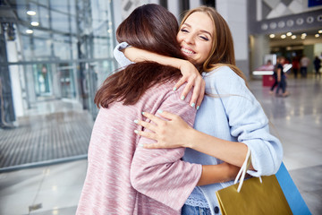 Portrait of two beautiful young women meeting in shopping center greeting each other and hugging both holding paper  bags with purchases