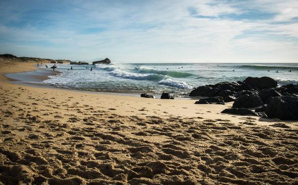 surfers catching powerful waves on atlantic ocean with breaking waves in blue sky, capbreton, les landes, france
