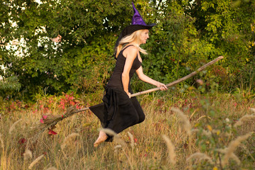 Young girl in witch costume flies on broomstick