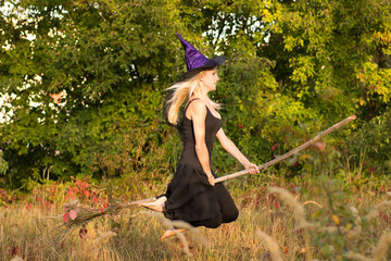 Pretty girl in witch costume flies on broomstick