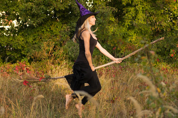 Adult girl in witch costume flies on broomstick