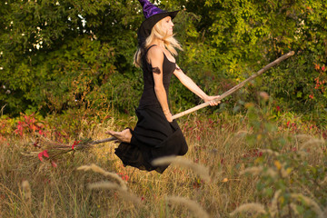 Active girl in witch costume flies on broomstick