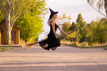 Joyful girl in witch costume flies on broomstick