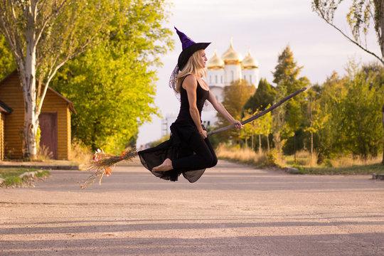 Joyful girl in witch costume flies on broomstick