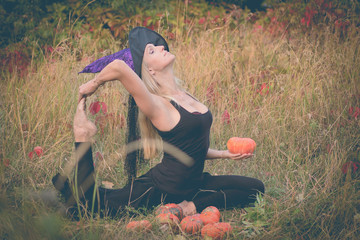 Adult woman in witch costume practicing yoga