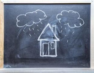House and clouds with rain chalk hand drawn on the middle of a blackboard with frame. Copy space for your text.