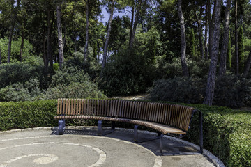 Half round curved crescent shaped bench in the park with trees and bushes in background