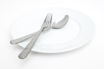 empty new ceramics plate with spoon and fork on white background