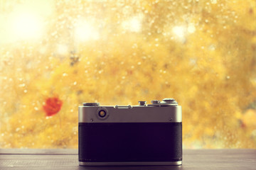 golden autumn season/ old retro camera is installed on the table for photographing the wet window after the rain