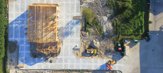 Aerial view wood frame house under construction with foundation in Humble, Texas, USA. New stick built framing one floor commercial building. Excavator, bulldozer and pile beams, logs, sand. Panorama