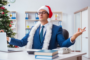 Businessman celebrating christmas holiday in the office