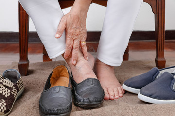 Elderly woman putting on shoes wrong feet