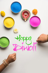 Stock Photo of happy diwali greeting card clicked using elements of Diwali festival like colourful rangoli in bowls, diwali clay lamp or diya and girl or girl making rangoli, writing happy diwali