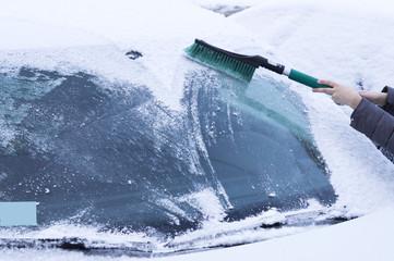 маленький мальчик очищает автомобиль от снега