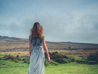 Beautiful young woman in dress on the moor
