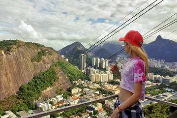 young blonde woman looking at Rio de janeiro aerial view