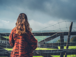 Woman by gate and fence in countryside