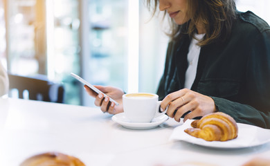 Fotomurales - Young woman holding in female hands mobile phone and drink hot aroma coffee or tea in breakfast time, hipster traveler girl in the morning using smartphone gadget; holiday relax white cafe