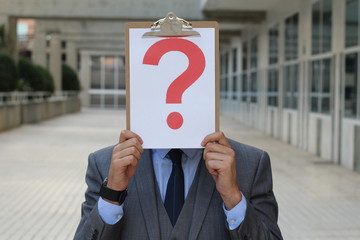 Businessman covering his face with a question mark