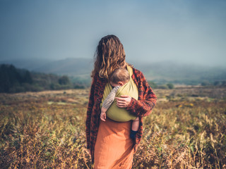 Young mother with baby in moor