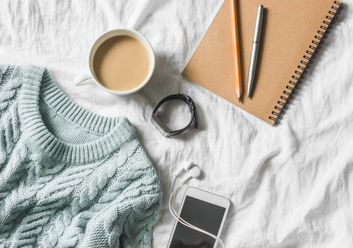 Blue knitted sweater, coffee with milk, notebook, headphones, smart phone on bed, top view. Women clothing. Flat lay