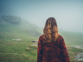 Young woman walking in the fog on moor