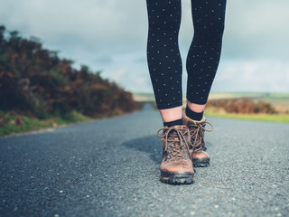Feet of young woman walking on country road
