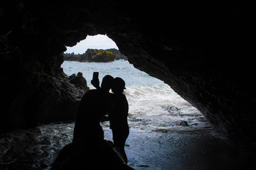 Couple Takes Selfie Silhouette in Cave with Ocean Background