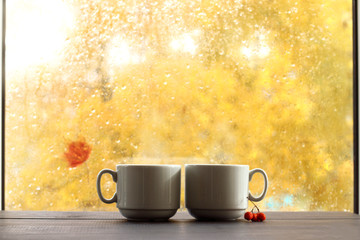 cozy atmosphere with nature view/ Two white cup of coffee on wooden table, against the window after rainy autumn