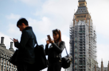 Tourists take pictures in Parliament Square, in front of the Elizabeth Tower housing the Big Ben bell, in central London