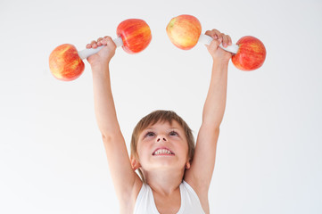 cheerful cute kid lifting dumbbells made from apples