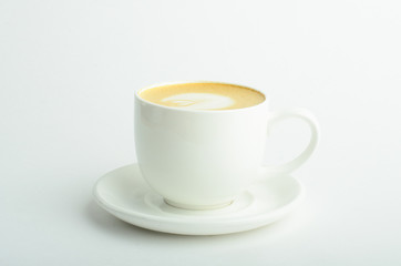 A cup of cappuccino coffee with heart shaped milk foam isolated on white background
