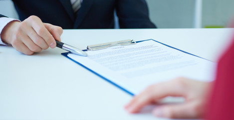 Closeup of businessman's hands showing  his new business partner the terms of the agreement or contract. Selective focus.
