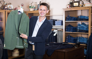 Smiling male customer searching new jacket