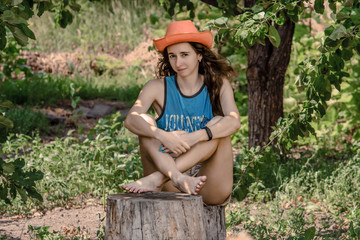 Portrait of pretty girl sitting on a stump. Dreamy young woman with orange cowboy hat the backdrop of the garden.