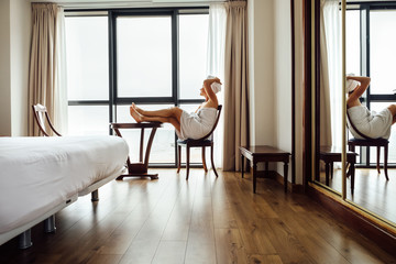 Woman after shower relax in hotel room near the panorame window