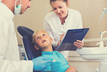 Dentist guy with assistant are diagnosticating to young patient which is sitting