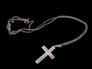 Silver cross, Christian jewelry, symbol, on black.