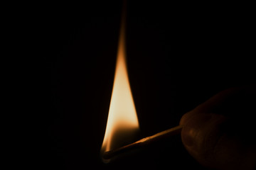 Burning match in the hand against the backdrop of darkness
