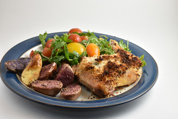 Healthy meal with roaster herb crusted chicken, multicolor fingerling potatoes, and arugula salad with heirloom tomatoes and lemon dressing.