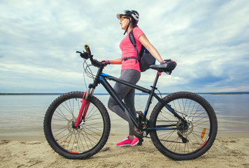 One young woman, an athlete in pink shoes, walks with a mountain bike in the morning on the river bank.