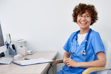 Portrait of friendly female doctor sitting at desk in office  and laughing happily, copy space